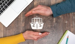 Concept of marine insurance with hands in a protective gesture