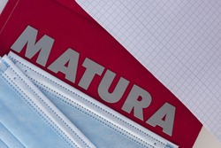 "Concept of matura exam during the pandemic. Closeup of the word ""matura"" and protective face masks."