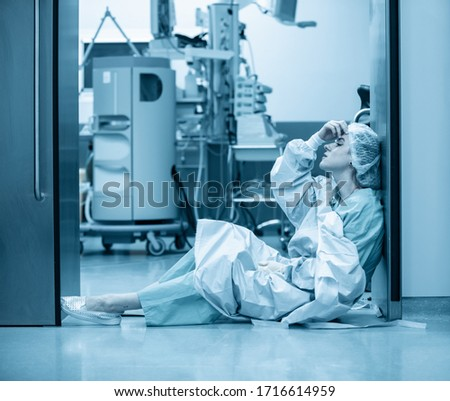 Concept of medecine surgery, Kovid 19. Tired, exhausted doctor after an exhausting shift in the intensive care unit. Pandemic, isolation, epidemic hard work of doctors, stay home. Blue monochrome Stok fotoğraf ©