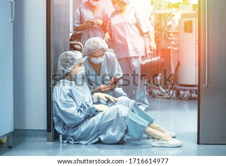 Concept of medecine surgery, Kovid 19. Tired, exhausted doctor after an exhausting shift in the intensive care unit. Pandemic, isolation, epidemic hard work of doctors, stay home. Stok fotoğraf ©