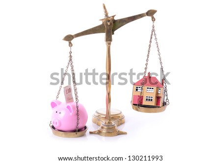 concept of mortgage and saving piggy bank and house on scales