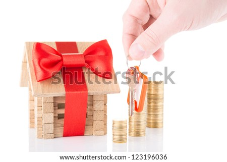 Concept of mortgage with keysin a hand and wooden house