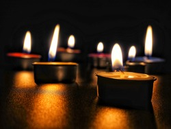 concept of mourning the dead from the corona virus represented by warm candles.COVID-19