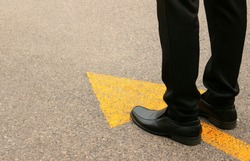 Concept of moving forward: Black leather shoes on a tarmac road with yellow direction arrow.