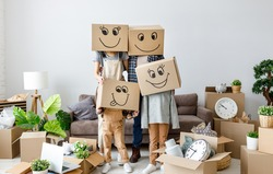 concept of moving to a new apartment and a mortgage. Unrecognizable couple and kids wearing carton boxes on heads standing together in new flat with various stuff during relocation