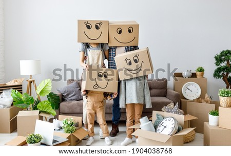 concept of moving to a new apartment and a mortgage. Unrecognizable couple and kids wearing carton boxes on heads standing together in new flat with various stuff during relocation Foto stock ©