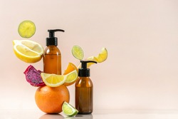 Concept of natural cosmetics product. Glass bottles with bodycare and skincare soap or lotion near levitate vitamin fruits isolated on pastel pink background with copy space