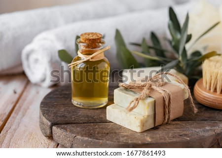Concept of natural ingredients in cosmetology for gentle skin care. Organic olive oil in glass bottle, handmade soap bars. Atmosphere of serenity and relax. Rustic wooden background, close up. Foto stock ©