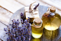 Concept of natural organic oil in cosmetology. Moisturizing skin care and aromatherapy. Gentle body treatment. Handmade soap. Atmosphere of harmony relax. Wooden background, lavender flower copy space