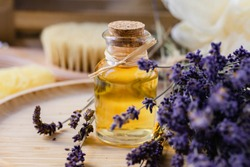 Concept of natural organic oil in cosmetology. Moisturizing skin care and aromatherapy. Gentle body treatment. Atmosphere of harmony relax. Wooden background, lavender flower, brush, soap. Close up