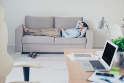 Concept of necessity of  having a rest while working. Tired exhausted manager clothed in formal-wear is sleeping on a sofa in his modern office