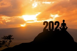 Concept of New 2021.silhouette of woman yoga on the mountain with 2021 year.