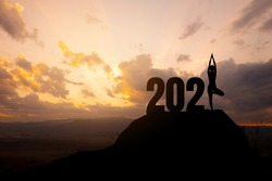 Concept of New 2021.silhouette of woman yoga stand on the mountain with 2021 year.
