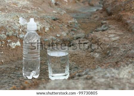 concept of of water shortage - a hand with an empty bottle on the background of dried ground