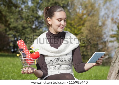 Concept of on line shopping- cute girl thinks what to shop online- with tablet PC and shopping trolley
