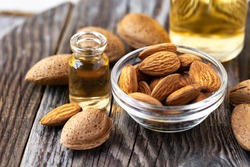 Concept of organic vegetable oils for cooking and cosmetology. Almond nuts to illustrate ingredients. Rustic wooden background, natural oil in glass bottles. Close up, macro