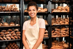 Concept of own business. Young adult female working in small family bakery, standing near shelves with fresh wholegrain bread and smiling wide