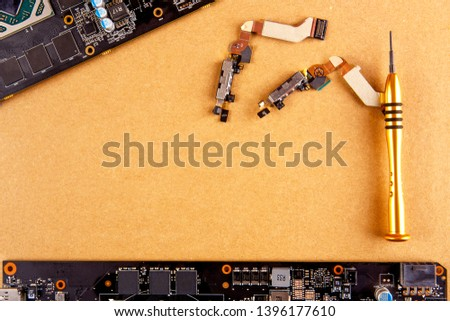 Concept of parts for mobile phones. Mobile board, screwdriver and plume for repair of mobile phones lie  on the background of a cardboard box, spare parts for mobile phones