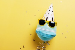Concept of party during covid-19. Invitation card with blue ballon with protective mask, party hat and sunglasses. Top down view with copy space