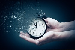 Concept of passing away, the clock breaks down into pieces. Hand holding analog clock with dispersion effect