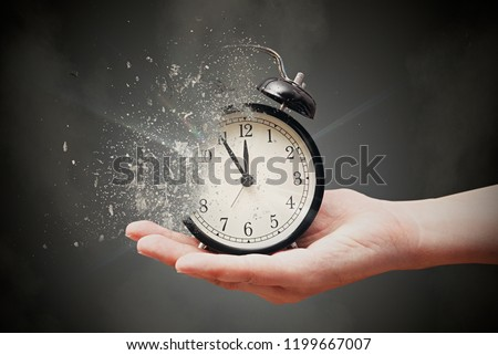 Concept of passing away, the clock breaks down into pieces. Hand holding analog clock with dispersion effect #1199667007