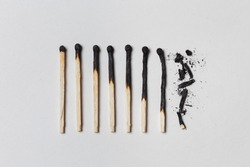 Concept of patience. A row of burnt matches, from left to right, from almost a whole match to a completely burnt match to the dust. White background, flat lay.