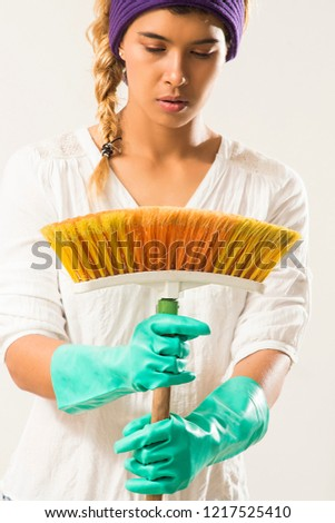 Concept of people, housework and housework: Housewife sweeping with dense bristle broom #1217525410