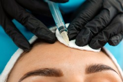 Concept of plastic surgery. Close-up of female's head getting injection in the cosmetology salon. Cosmetologist in latex gloves with syringe injects a botulinum toxin in forehead.