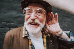 Concept of positive mood lifestyle of hearing impaired person. Close up portrait of happy pensioner with playful glance holding palm near his ear