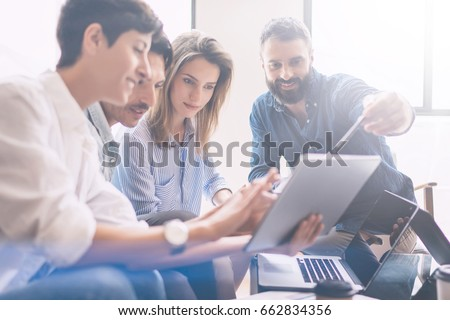 Concept of presentation new business project.Group of young coworkers discussing ideas with each other in modern office.Business people using electronic devices.Horizontal, blurred background #662834356