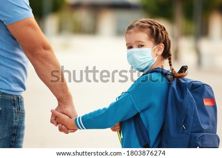 Concept of preventing a coronavirus covid-19 and viral infections. Father escorts a   daughter schoolgirl   in a medical mask to school