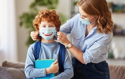 Concept of preventing a coronavirus covid-19 and viral infections. Mother puts on medical mask with painted smile   little son schoolboy before leaving home for school