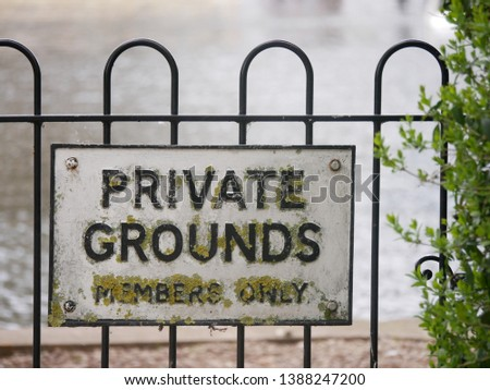Concept of privacy or security shown by vintage sign saying Private Grounds members only in capital letters covered in lichen on a fence beside the River Thames in Stratford