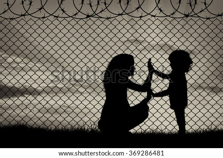 Concept of refugee. Silhouette of mother and child refugees at the border fence at sunset Foto stock ©