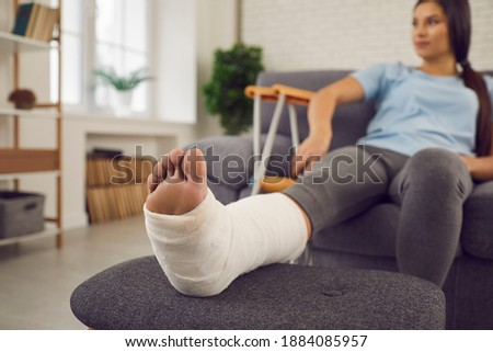 Concept of rehabilitation of people after serious physical accident injury. Female patient with broken leg in plaster cast sitting on sofa. Young woman with foot bone fracture resting on couch at home Photo stock ©