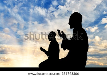 Concept of religion Islam. Silhouette of two men praying at sunset