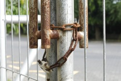 Concept of Security: An old  locked fence with rusty chain and padlock