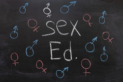 Concept of sex education on the blackboard, female and male sign.