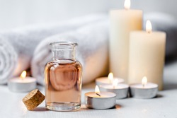 Concept of spa treatment in salon. Natural organic oil, towel, candles as decor. Atmosphere of relax, serenity and pleasure. Anti-stress and detox procedure. Luxury lifestyle. White wooden background
