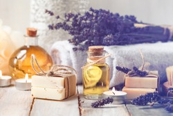 Concept of spa with natural organic oil. Moisturizing skin care and aromatherapy. Gentle body treatment. Handmade soap. Atmosphere of harmony, relax. Wooden background, lavender flowers, candle