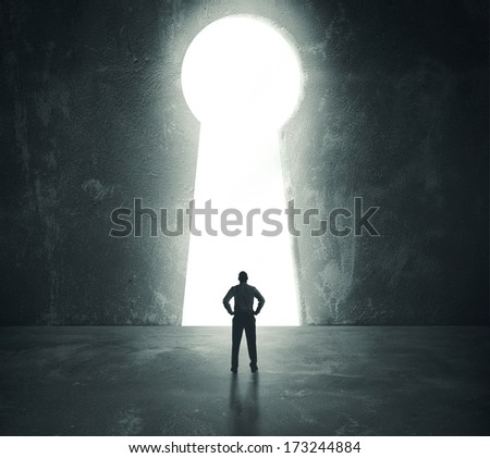 Concept of success with businessman looking through key hole