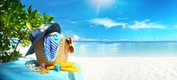 Concept of summer beach holiday on tropical island Maldives. Beach bag, blue hat with frangipani flowers, glasses, yellow Slippers, towel against the sky, white sand and turquoise ocean on Sunny day.