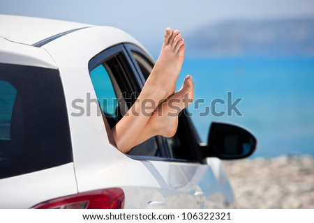 Concept of summer car trip vacation . Woman legs out the window in car at background of sea water. Conceptual travel ,freedom and holidays image.