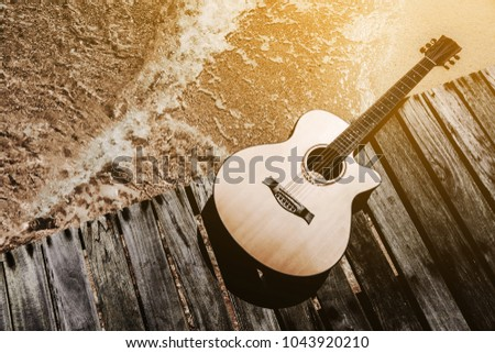 Concept of summer traveling with guitar on beach background.