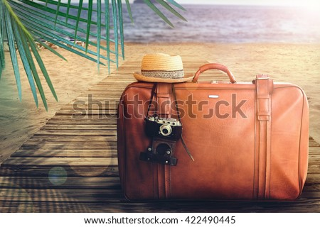 Concept of summer traveling with old suitcase on blur beach background.