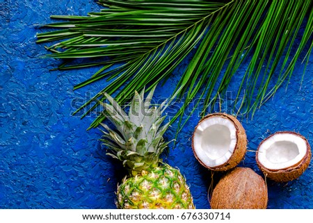 Concept of summer tropical fruits. Pineapple, cocount and palm branch on blue table background top view copyspace #676330714