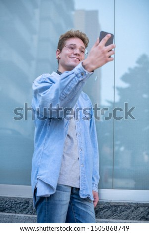 Concept of technological youth. Bottom view of a handsome smiling man with glasses and headphones taking a picture of himself with his smart cell phone. Portrait