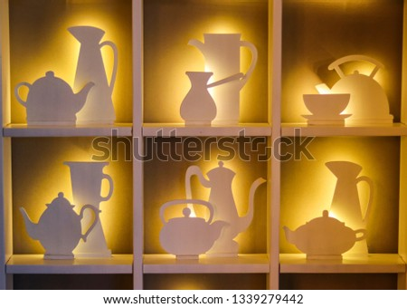 concept of the interior design of the cafe. The contours of the cups and teapots illuminated on a dark background. #1339279442