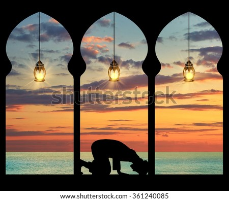 Concept of the Islamic religion. Silhouette of praying Muslim at the background of the sea sunset