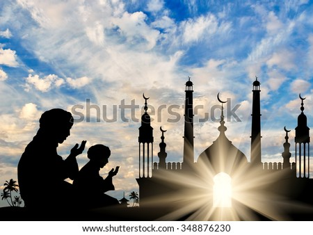 Concept of the Islamic religion. Silhouette of two men praying on the background of the town hall at dawn